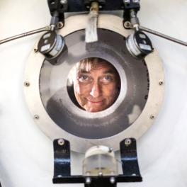 Terry Kerby peers through the porthole of a Pisces V research submersible. Image courtesy of Kent Nishimura for The New York Times.
