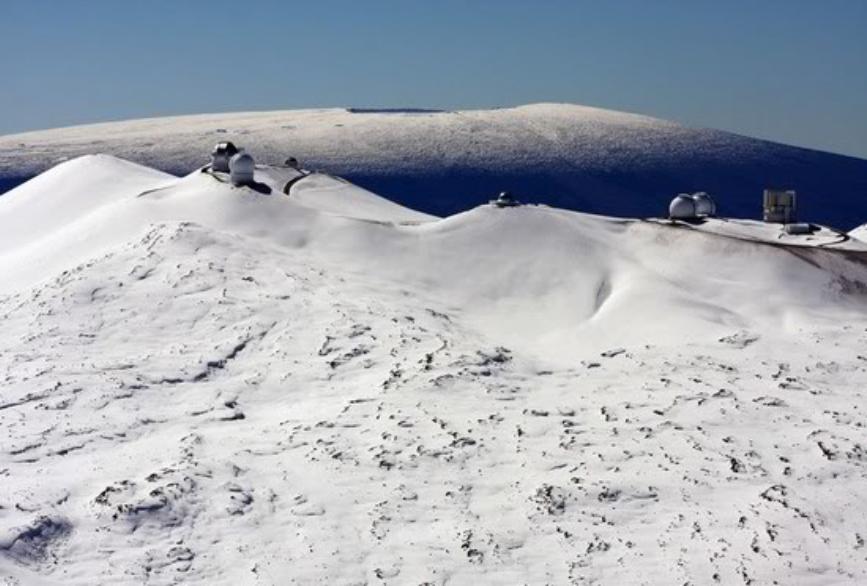 The view from snow-covered Mauna Kea across to a snowy Mauna Loa, Hawaiʻi.