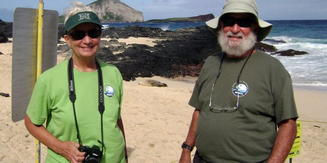 Marilyn and DB Dunlap in front of a sunbathing Hawaiian Monk Seal.