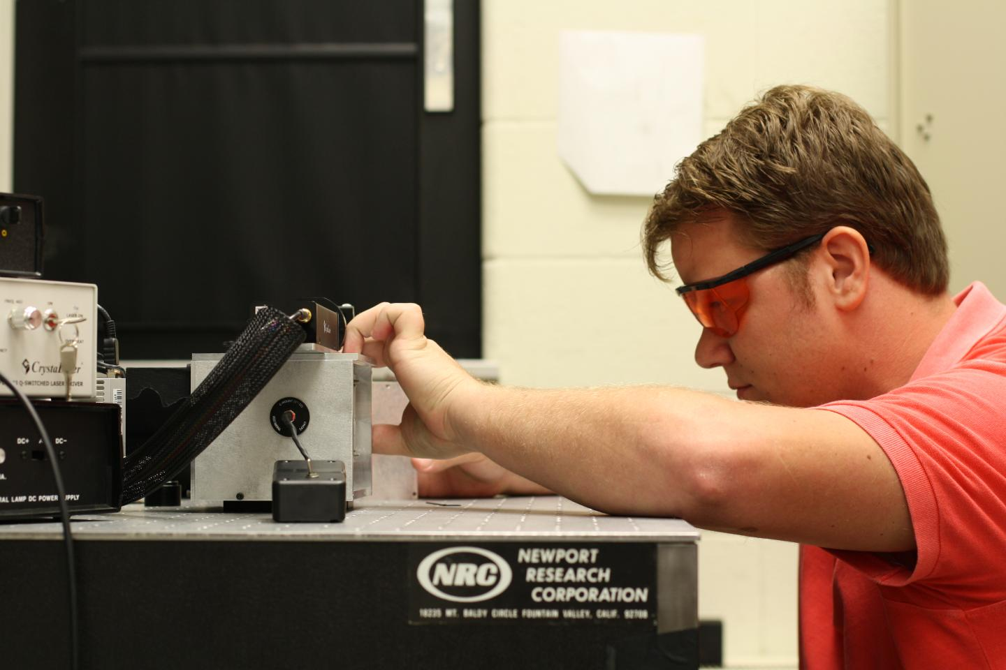 Derek Davis, a student from Old Dominion University, working on micro Raman spectroscopy instrument.