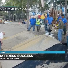Screen shot from Hawaii News Now report showing sand mattress being installed on the shoreline in Waikiki.