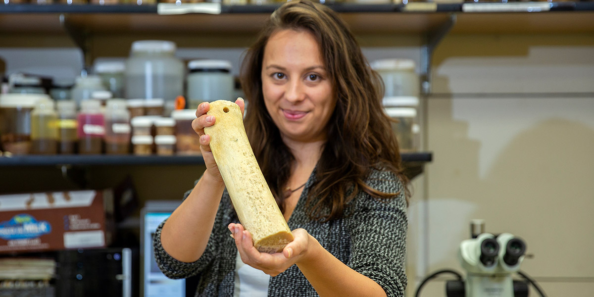 Emily Young holding a whale bone. Photo credit: UH Foundation.