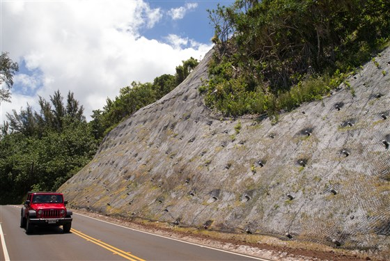 A wire netting covers a hillside to prevent rockslides on Kūhiō Highway near Hanalei, Hawaii.