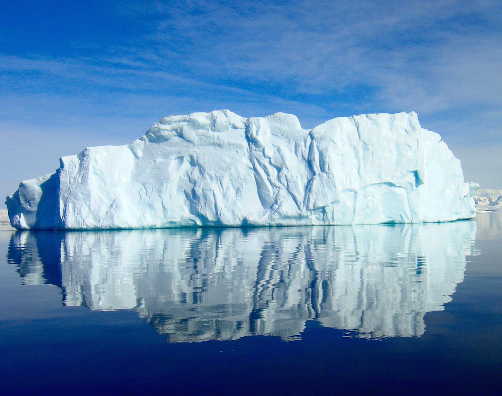 An iceberg floats off the Antarctic Peninsula in calm waters. Credit: Jeffrey Kietzmann, NSF.