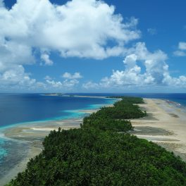 Low-lying windward reef islands of Majuro atoll. A narrow strip of vegetation is visible in the middle of a low, narrow island