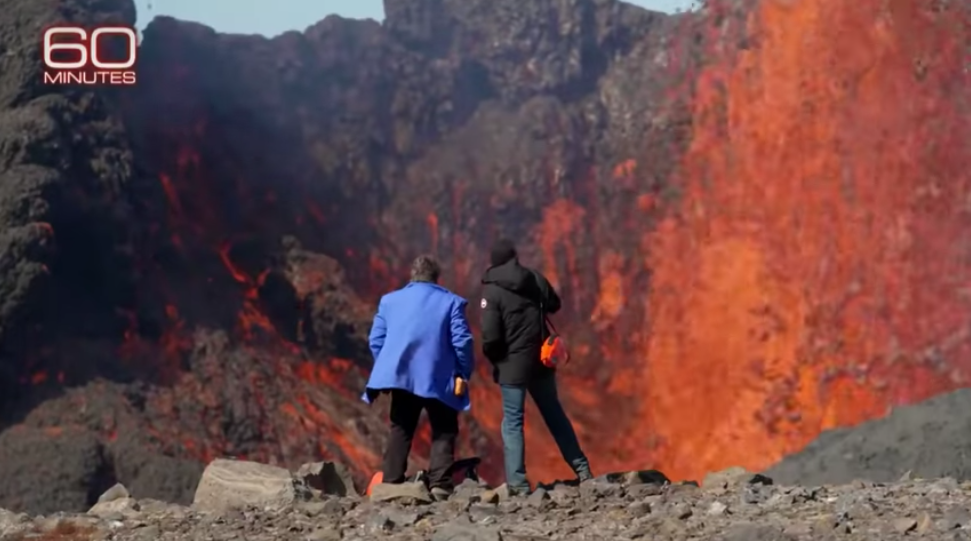 Thorvaldur Thordarson and Bill Whitaker in front of erupting volcano in Iceland.