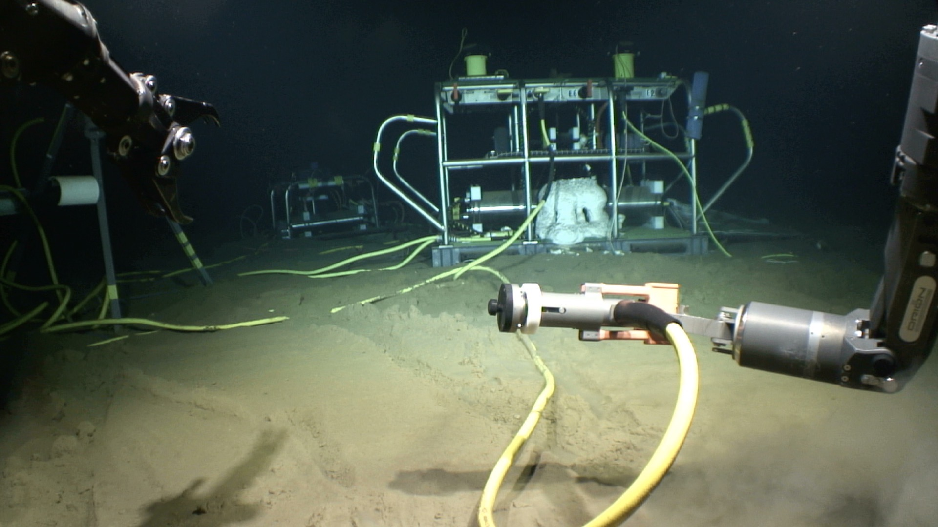 Instrumentation on the seafloor at the Aloha Cabled Observatory with ROV Lu'ukai manipulator arms in view.