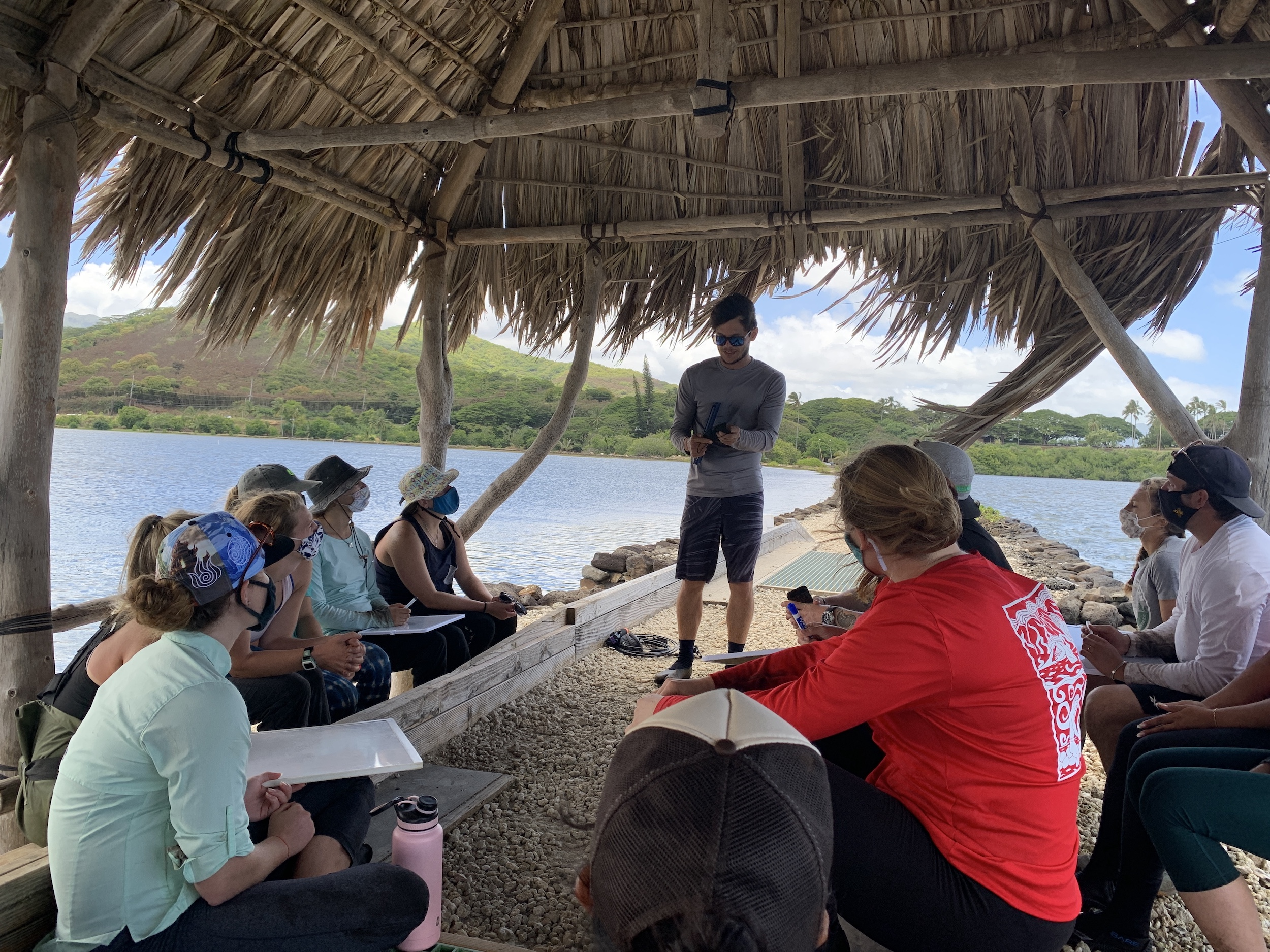 From the wall of Heʻeia Fishpond, MBGP students learn about the history of the Heʻeia ahupuaʻa from Fred Reppun.